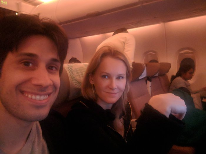 Pablo and Karen on a flight, smiling. Click for full-size image.