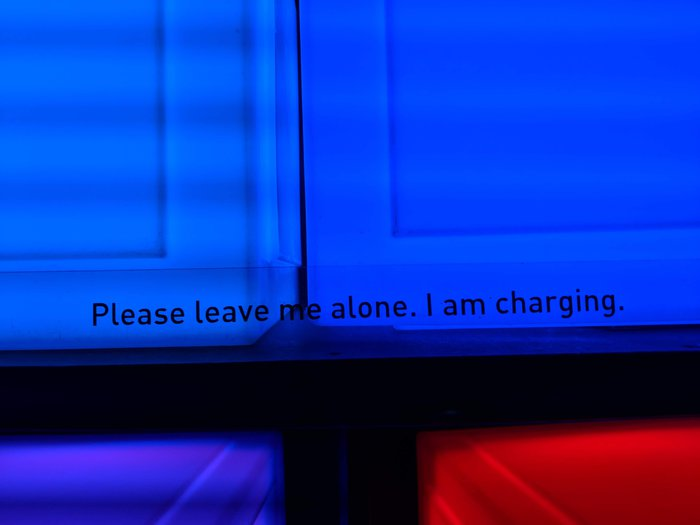Glowing cube that says 'Please leave me alone. I am charging.' Click for full-size image.