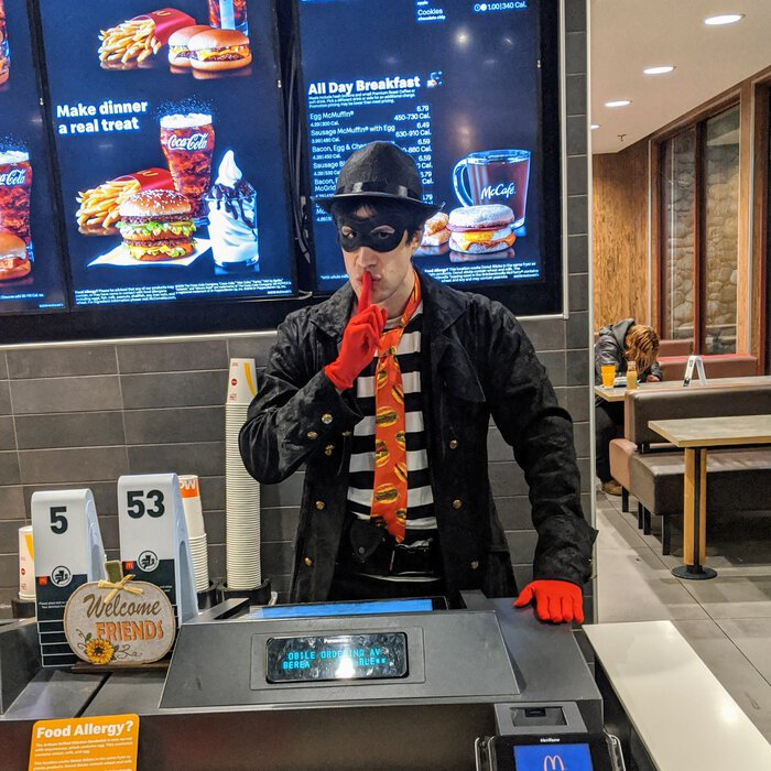 Pablo dressed as the Hamburglar, behind the counter at a McDonalds, looking mischevious. Click for full size.
