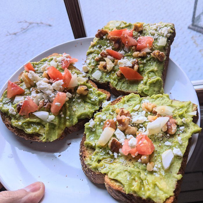 Avocado toast with walnut, onion, tomato, and feta.