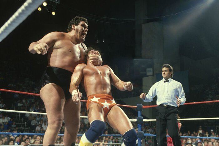 Andre the Giant, looking Giant over someone who is rather large themselves.