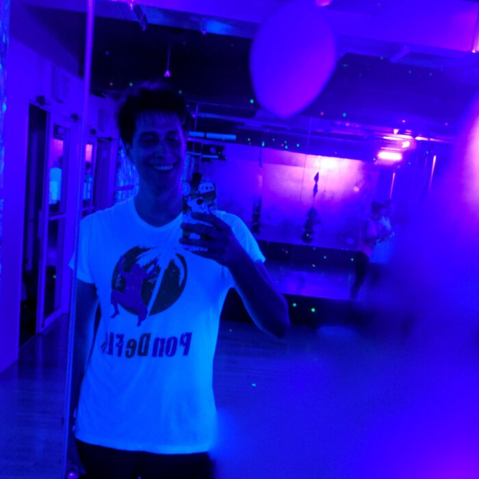 Pablo mirror selfie, sweaty in a blacklight dance studio.