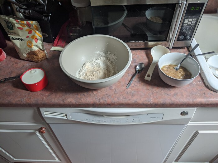 Ingredients at the ready: a mixing bowl with dry powders, and a bowl with mashed bananas and wet ingredients.